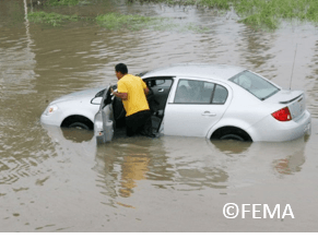 Map pushing his car in deep flooding water